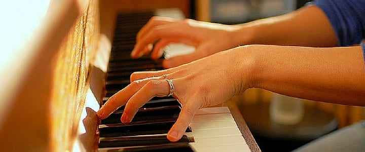 a woman playing the piano with proper piano hand position