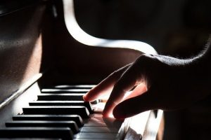 a man plays an upright piano